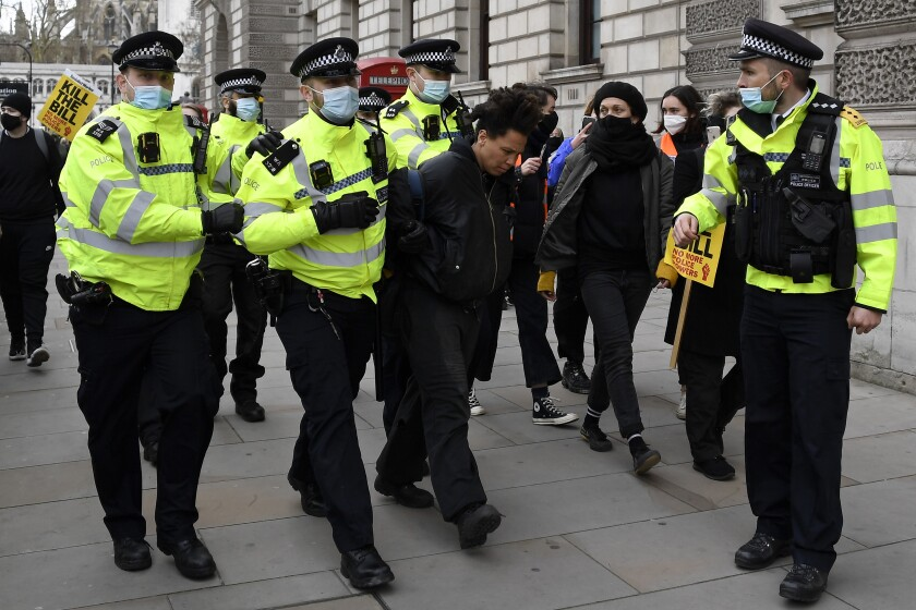 Police detain a man for blocking traffic at Parliament Square during a 'Kill the Bill' protest in London, Saturday, April 3, 2021. The demonstration is against the contentious Police, Crime, Sentencing and Courts Bill, which is currently going through Parliament and would give police stronger powers to restrict protests. (AP Photo/Alberto Pezzali)