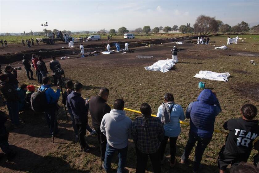 Expertos forenses registran la zona cerca de una toma clandestina de gasolina de Petróleos Mexicanos (Pemex) que explotó este sábado, en Tlahuililpan, Hidalgo (México). EFE