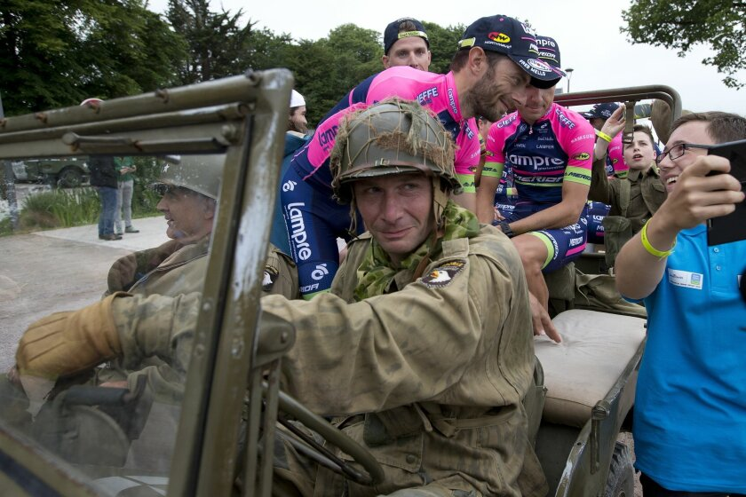 A teenager takes a selfie with team Lampre Merida as they ride in a World War II vehicle  during the official team presentation two days before the start of the Tour de France cycling race in Sainte-Mere-Eglise, France, Thursday, June 30, 2016. (AP Photo/Peter Dejong)