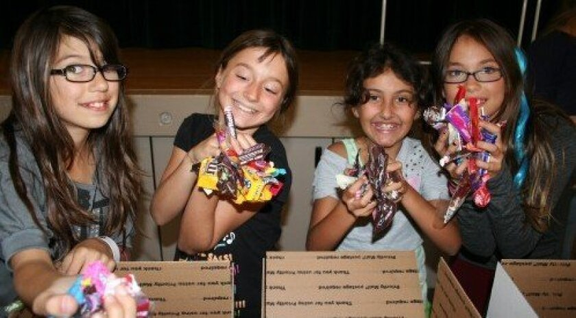 Rosa Revas, Seren Kremer, Eilee Shahidi and Katherine Critsei show off the candy donated to the troops. (Photo: Karen Billing)