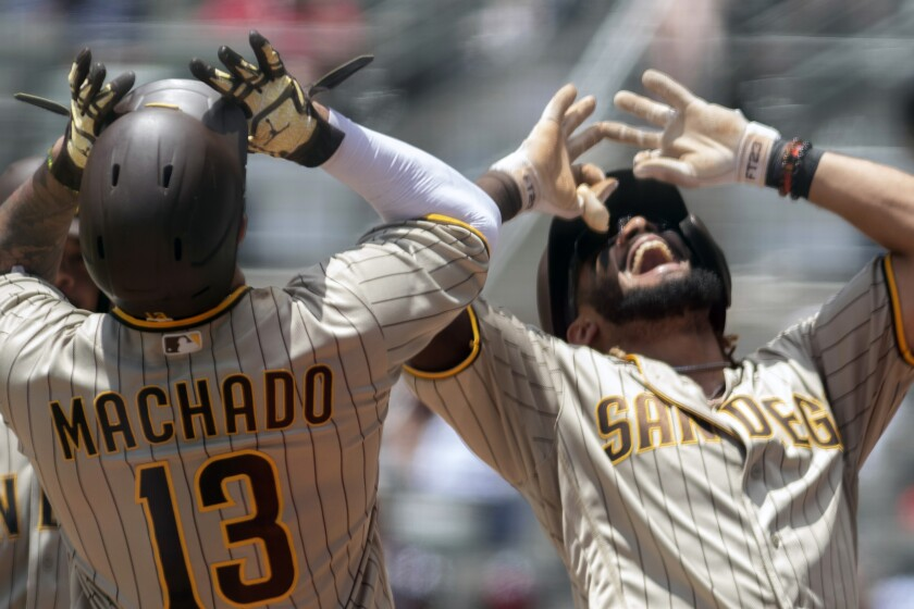 San Diego Padres third baseman Manny Machado (13) and Padres shortstop Fernando Tatis Jr. celebrate a two-run home run by Tatis against the Atlanta Braves in the fifth inning in the first game of a baseball doubleheader Wednesday, July 21, 2021, in Atlanta. (AP Photo/Hakim Wright Sr.)
