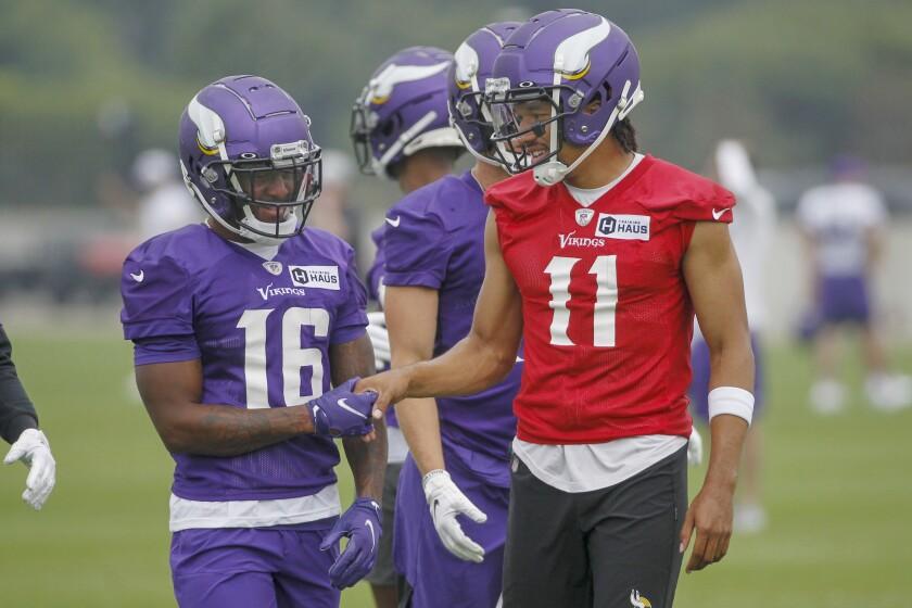 Minnesota Vikings wide receiver Whop Philyor (16) and quarterback Kellen Mond (11) enjoy a good play during NFL football training camp Friday, July 30, 2021, in Eagan, Minn. (AP Photo/Bruce Kluckhohn)