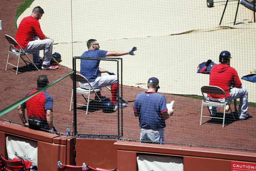 FILE - In this July 5, 2020, file photo, Boston Red Sox players sit apart for social distancing during baseball practice at Fenway Park in Boston. Public health experts have mixed feelings about baseball's hopes to open its season July 23. There is optimism because of the nature of the sport itself, which produces less on-field risk than basketball, football or hockey. Then again, players and their families face a daunting task staying safe away from the ballpark, especially with teams traveling to and from hard-hit regions including Florida and Texas. (AP Photo/Michael Dwyer)