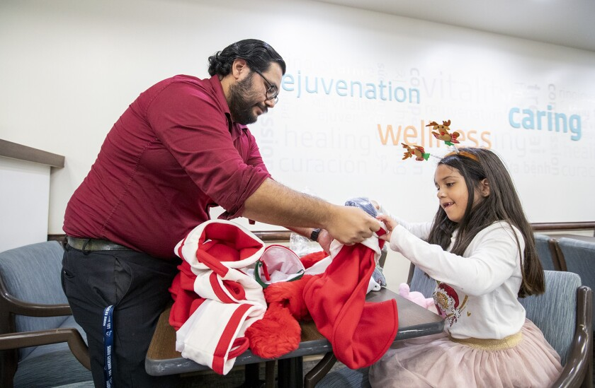 Natalie Cervantes, 6, and her dad, Anthony, stuff stockings for families in the neonatal intensive care unit at Fountain Valley Regional Hospital and Medical Center. Cervantes was born six weeks premature and spent her fist days in the NICU.