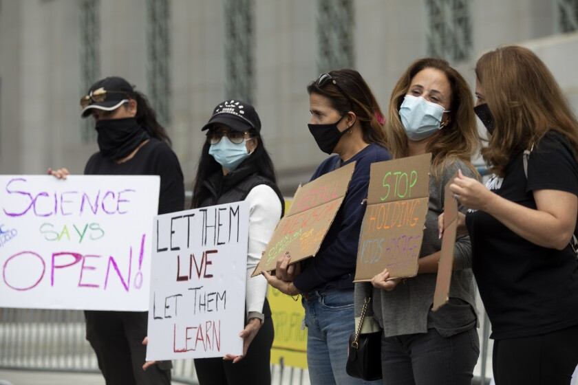 Five people holding signs and wearing masks