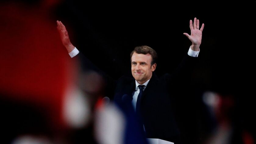 TOPSHOT - French president-elect Emmanuel Macron waves to the crowd as he delivers a speech at the P