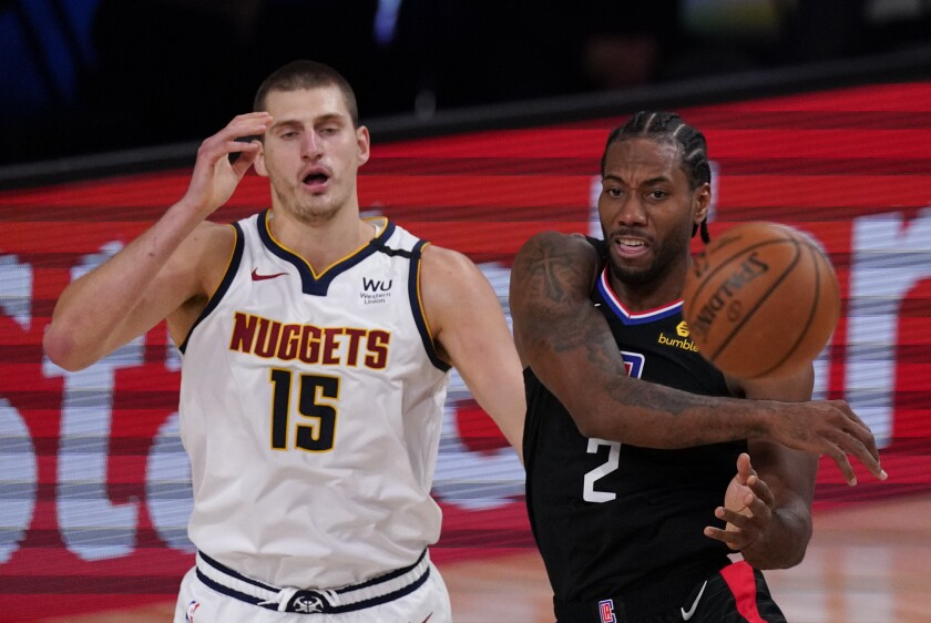 The Clippers' Kawhi Leonard passes in front of the Nuggets' Nikola Jokic on Sept. 5, 2020.