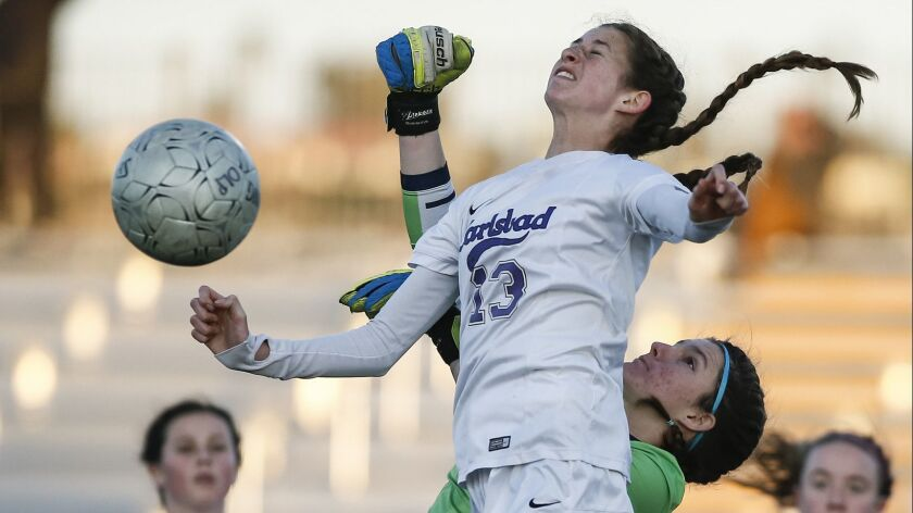 Carlsbad forward Lexi Wright (13) and OLP goalkeeper Grace Kotnik (0) collide while going for a ball in the first half.