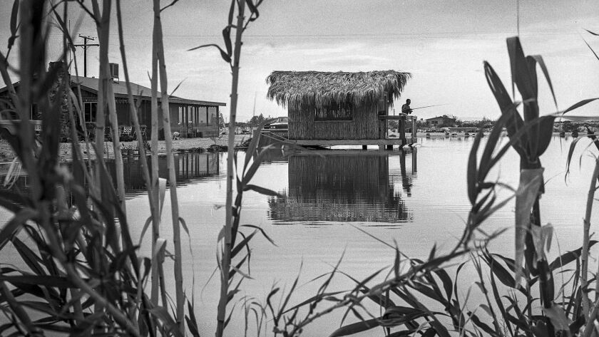 March 27, 1965: Eugene Cowell fishes from a tiki house in his one-acre lake, one of the 35 that blossomed in the desert community of Newberry. He says catfish eat from his wife's hand.