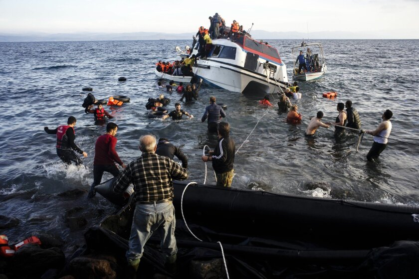 Volunteers and local residents help refugees and migrants disembark from a small vessel after their arrival in Skala Sykaminias on the northeastern Greek island of Lesbos on Friday, Oct. 30, 2015. Greek authorities say a number of people have died near other islands after two boats carrying migrant
