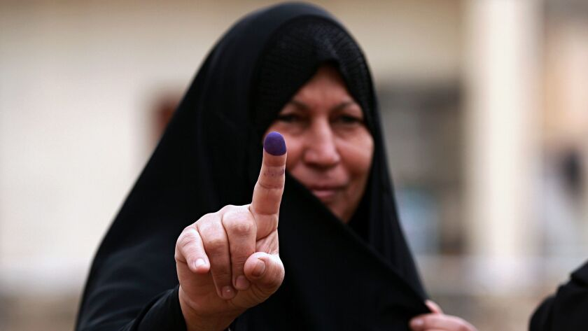FILE - In this May 12, 2018 file photo, an Iraqi woman shows her ink-stained finger after casting he