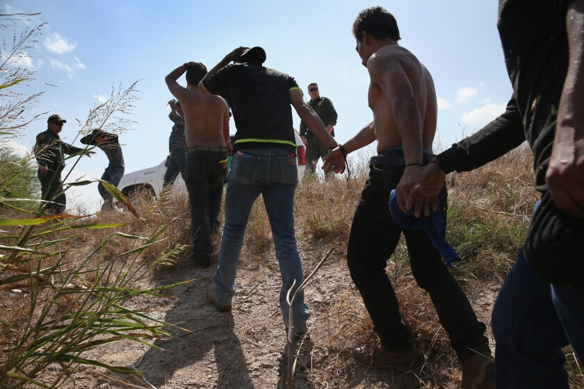 U.S. Border Patrol agents detain undocumented immigrants after they crossed the border from Mexico into the United States.