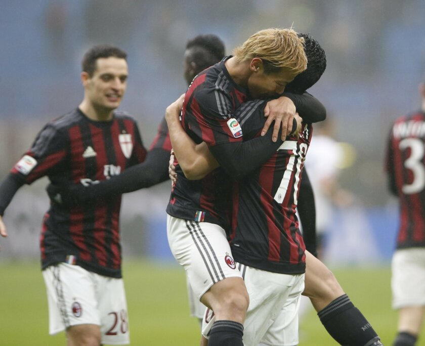 AC Milan's Carlos Bacca, right, celebrates with his teammate Keisuke Honda after scoring during a Serie A soccer match between AC Milan and Genoa, at the San Siro stadium in Milan, Italy, Sunday, Feb. 14, 2016. (AP Photo/Luca Bruno)