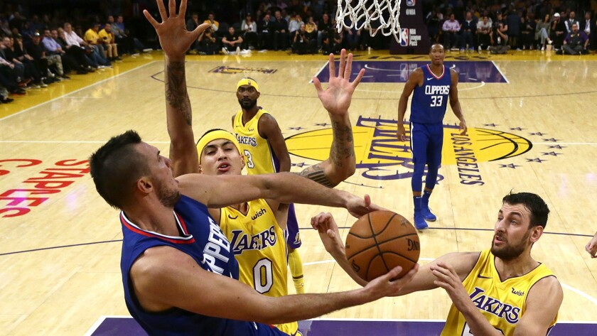 Clippers forward Danilo Gallinari is fouled by Lakers forward Kyle Kuzma as he drives to the basket during first half of their season opener.