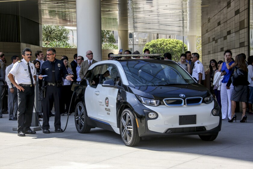 L.A. Fire Chief Ralph Terrazas, left, and LAPD Chief Charlie Beck on Friday check out a BMW electric vehicle at LAPD headquarters before a news conference at which the mayor offered up details about the city's plan to bolster the use of electric vehicles.