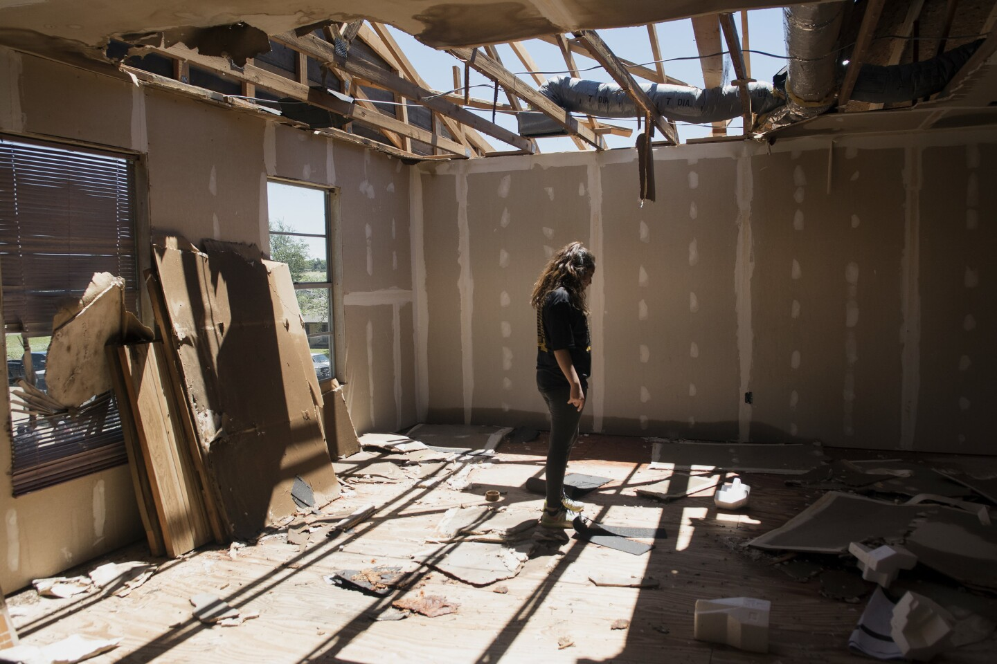 Stephanie Quezada looks at the damage to the second floor of her father's church, Primera Iglesia Bautista, in Canton, Texas, on April 30, 2017. Severe storms including tornadoes swept through several small towns in East Texas, killing several and leaving a trail of overturned vehicles, mangled trees and damaged homes, authorities said Sunday.
