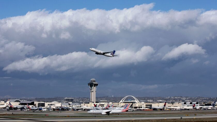 FILE- In this Nov. 27, 2016, file photo, a plane flies over Los Angeles International Airport. A $22