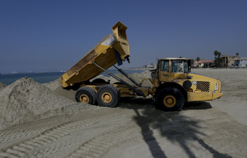 Dump trucks work to pile sand on a temporary berm to protect beach front homes on, Friday, Sept. 5, 2014, in Long Beach, Calif. Southern California is in for another round of high surf generated by what is currently Hurricane Norbert in the Pacific Ocean off Baja California. (AP Photo/Chris Carlson)