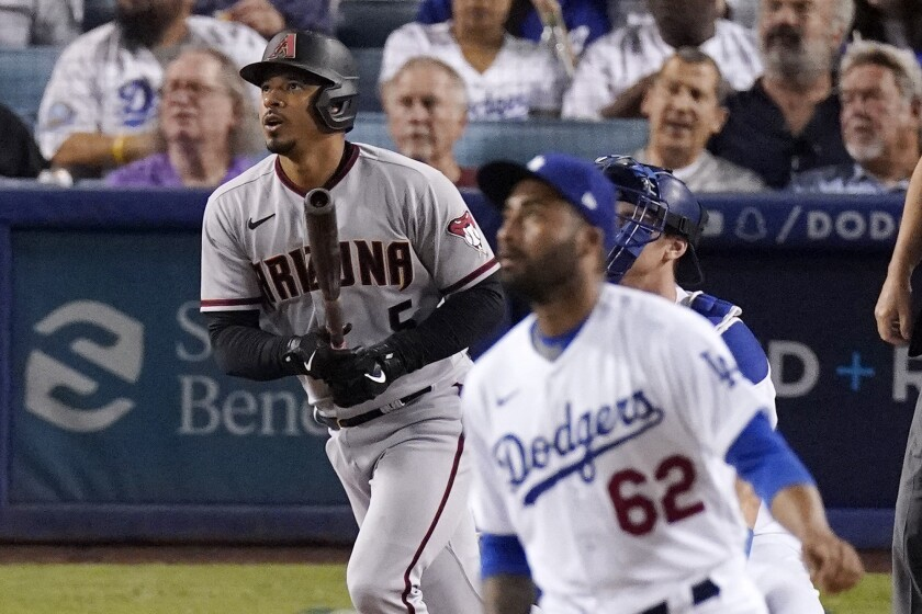 Arizona Diamondbacks' Eduardo Escobar, left, heads to first after hitting a two-run home run off Los Angeles Dodgers relief pitcher Darien Nunez, foreground, during the fifth inning of a baseball game Friday, July 9, 2021, in Los Angeles. (AP Photo/Mark J. Terrill)