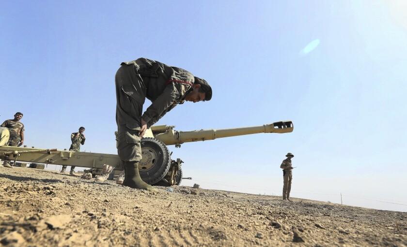 A Kurdish peshmerga fighter prays at a battlefield in a northern Iraqi village after Kurdish forces seized it from Islamic State militants.