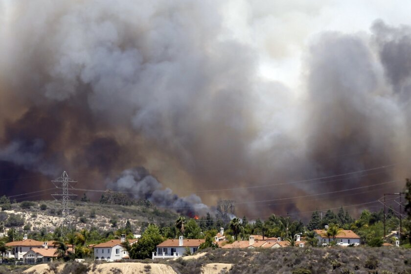 Wildfire climbs a canyon toward homes Wednesday, May 14, 2014, in Carlsbad, Calif. More wildfires broke out Wednesday in San Diego County — threatening homes in Carlsbad and forcing the evacuations of military housing and an elementary school at Camp Pendleton — as Southern California is in the gri