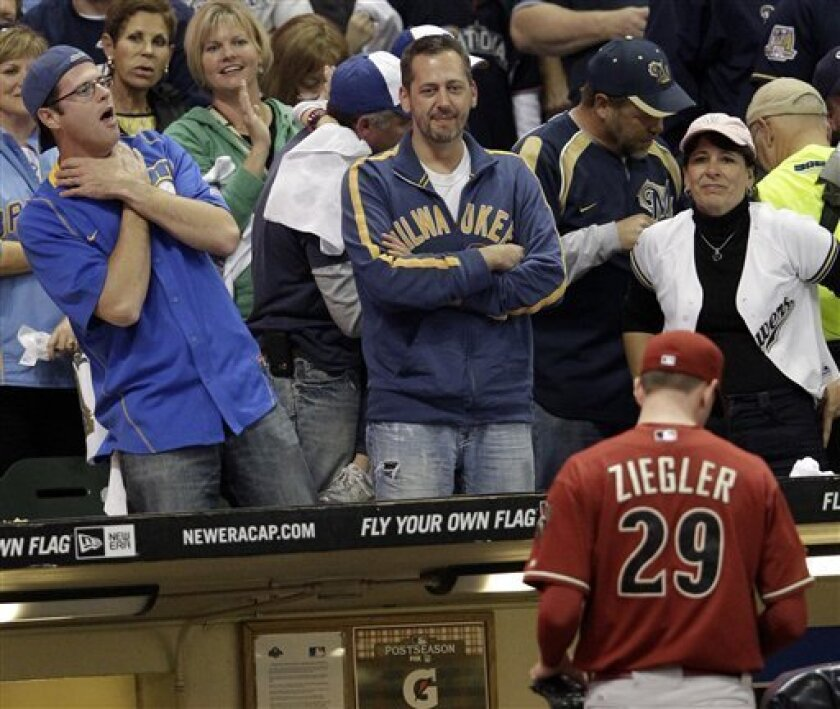 Fans react as Arizona Diamondbacks relief pitcher Brad Ziegler (29) leaves the game during the sixth inning of Game 2 of baseball's National League division series against the Milwaukee Brewers Sunday, Oct. 2, 2011, in Milwaukee. (AP Photo/David J. Phillip)