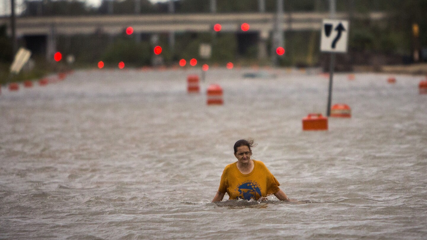A woman walks along a flooded street after leaving her homeless encampment that was washed away by Hurricane Matthew in Savannah, Ga.