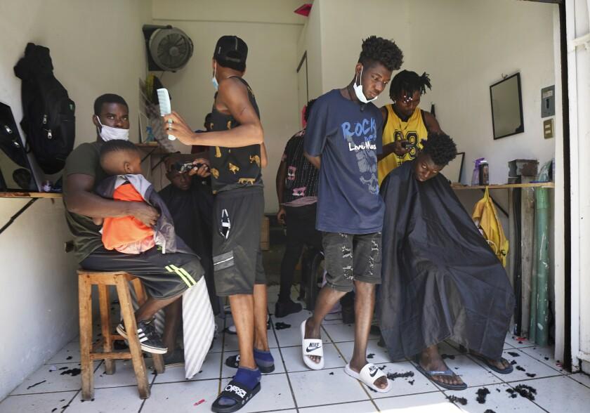 ARCHIVO - En esta foto de archivo del 3 de setiembre de 2021, migrantes haitianos están en una peluquería improvisada en Tapachula, México. Miles de migrantes, en su mayoría haitianos, están varados en la ciudad sureña de Tapachula. Muchos esperan meses, hasta un año, para que procesen sus pedidos de asilo. (AP Foto/Marco Ugarte, File)