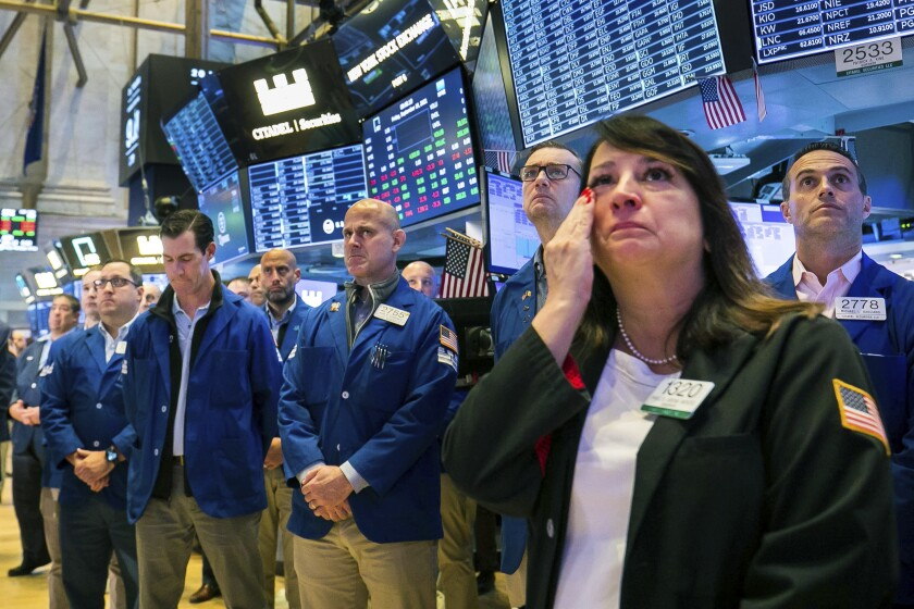 A woman wipes tears from her face. In the background, a row of solemn people stand at the New York Stock Exchange.