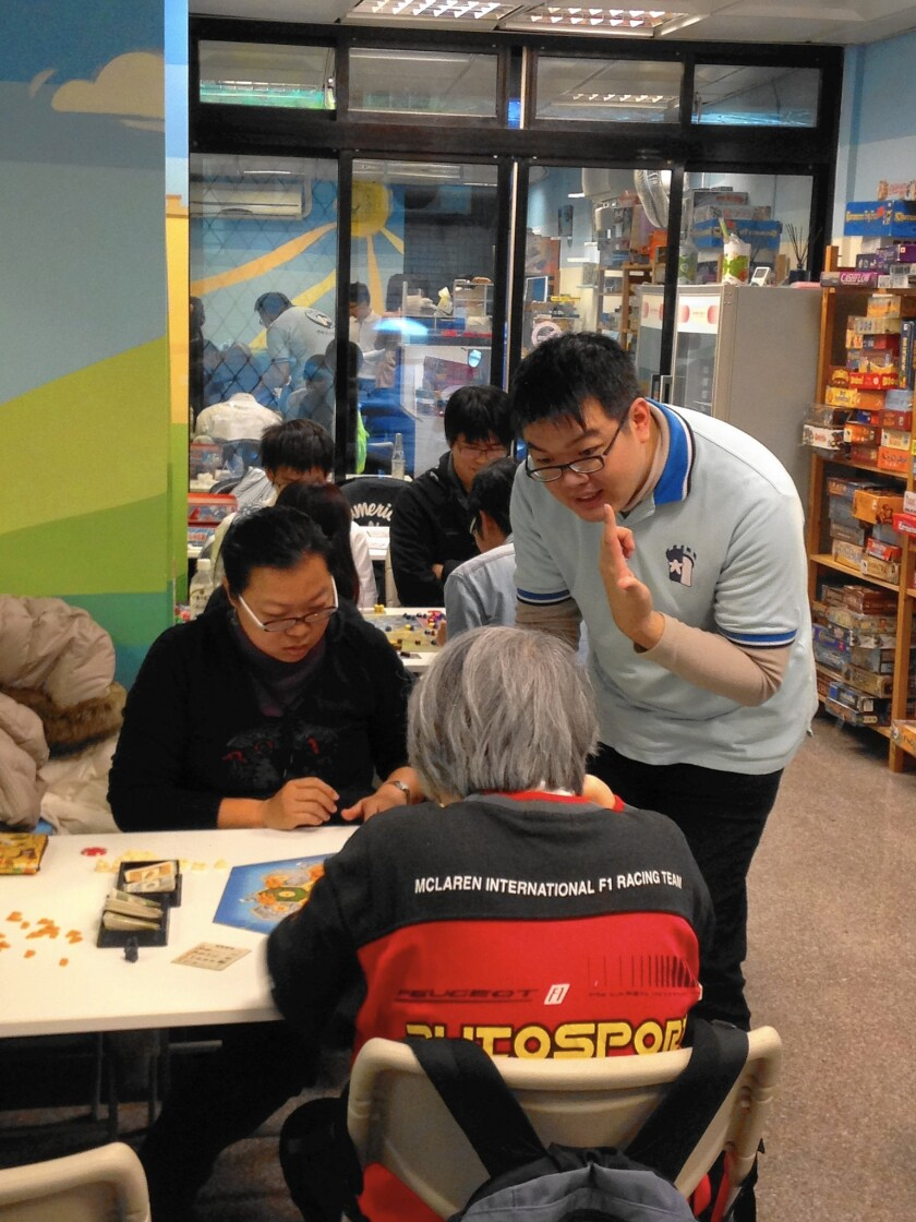 Lo Kuei-hua, manager of a Taipei board game parlor, shows customers how to play one of the 200 games he has in stock.
