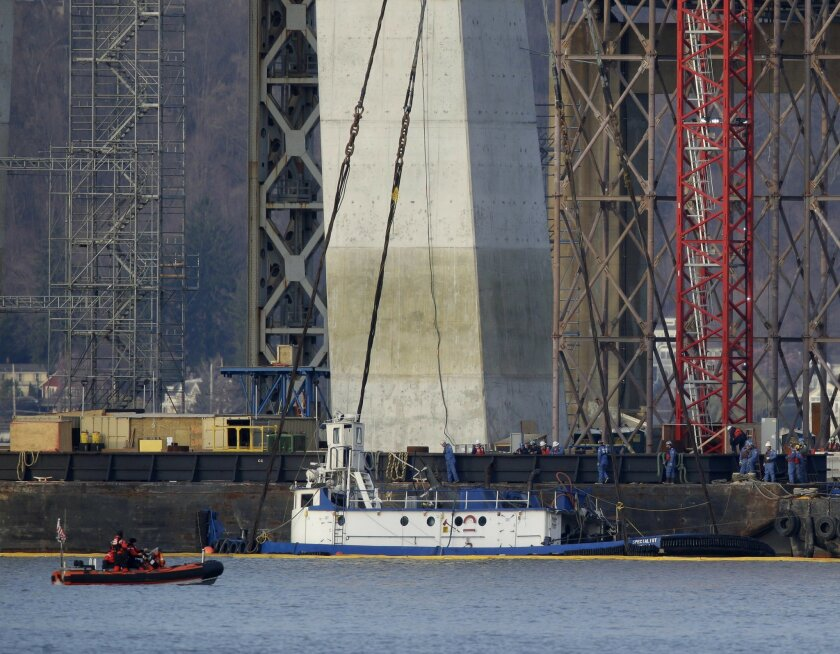 """The tugboat """"Specialist"""" is raised out of the water under the Tappan Zee Bridge with a massive crane in Tarrytown, N.Y., Thursday, March 24, 2016. The tugboat crashed and sank in the Hudson River north of New York City on March 12,, killing three crew members. (AP Photo/Seth Wenig)"""