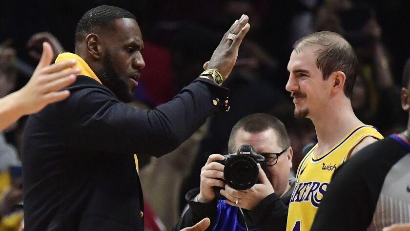Lakers forward LeBron James, left, congratulates guard Alex Caruso after a win over the Clippers last season.