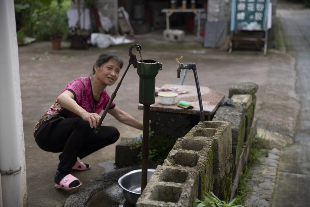 A villager pumps water from a well in Xixinan village, Anhui province.