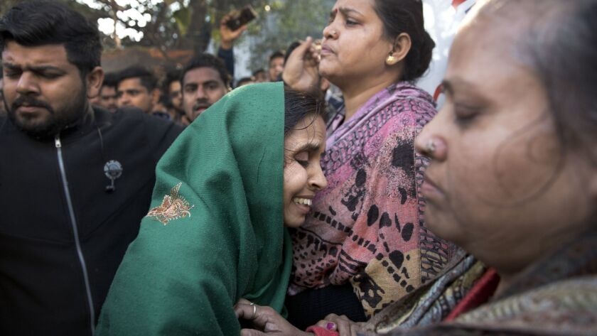 Relatives gather outside after an early morning fire killed more than a dozen people at a hotel in the Karol Bagh neighborhood of New Delhi on Tuesday, Feb. 12, 2019.