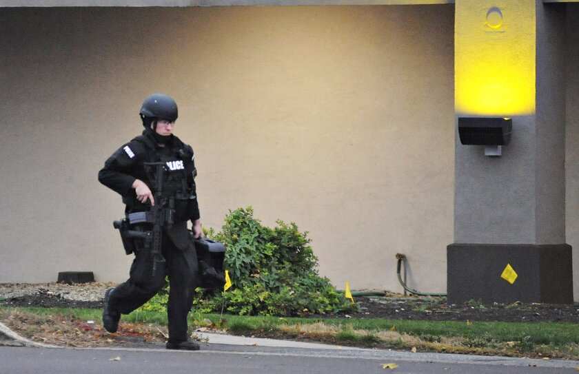 A police officer walks in front of Knights Inn after reports of a shooting in Bensalem Township near Trevose, Pa., Saturday, Nov. 7, 2015. Police seeking someone on a parole violation stumbled upon another man and a woman who were wanted in a double homicide in North Carolina — and that man is dead