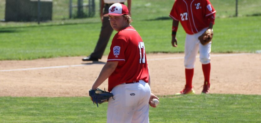 Encinitas Juniors hurler Nathan Laumann checks on a runner before delivering a pitch in a West Regional contest earlier this month in Vancouver, Wash. Infielder Sean Alvarez is at right.