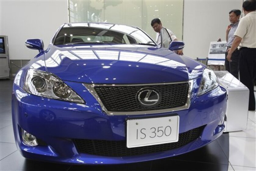 Visitors look at the Toyota Lexus IS 350 at a Toyota showroom in Tokyo Thursday, July 1, 2010. Toyota Motor Corp. said Thursday about 270,000 cars sold worldwide, including luxury Lexus sedans, have faulty engines, the latest quality lapse to hit the automaker following massive global recalls. (AP Photo/Shizuo Kambayashi)