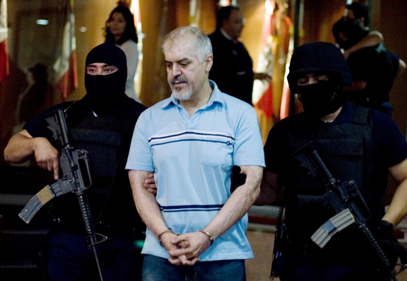 """Eduardo Arellano Felix, also known as """"The Doctor,"""" center, is escorted by masked police officers in Mexico"""