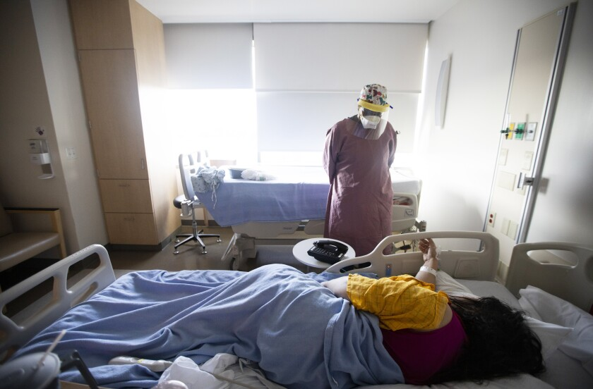 A nurse in a mask and face shield stands beside the bed of a patient