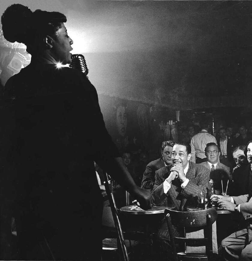Ella Fitzgerald sings to a crowd including Duke Ellington, center, and Benny Goodman, right of Duke, in New York City in 1948.