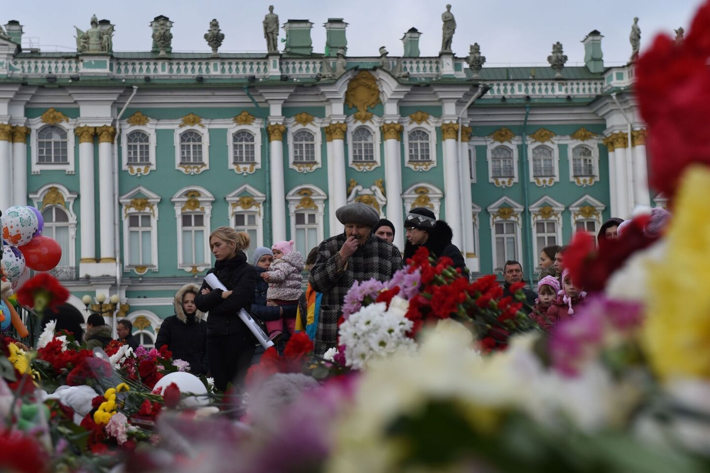 People stand in front of flowers at Dvortsovaya Square in central St. Petersburg in memory of the victims of a jetliner crash. Russian airline Kogalymavia's flight 9268 crashed en route from Sharm el-Sheikh to Saint Petersburg on October 31, killing all 224 people on board.