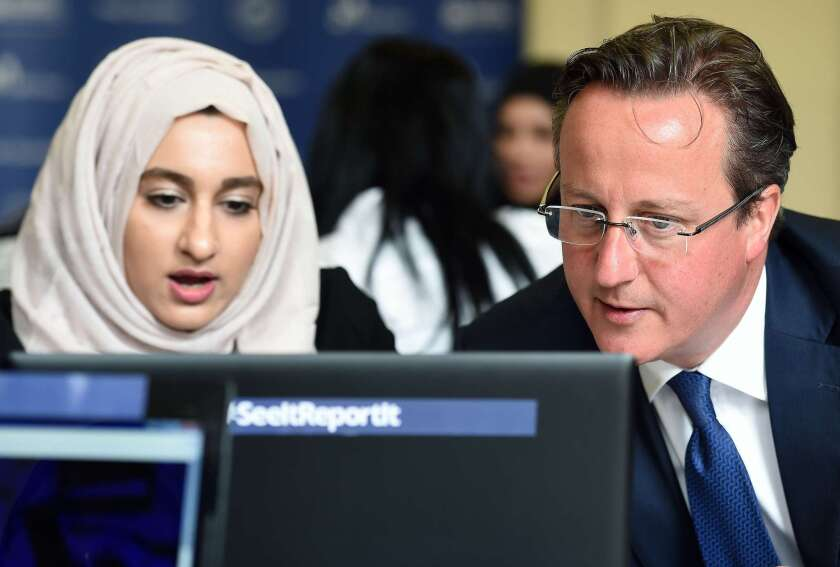 British Prime Minister David Cameron, visiting Ninestiles Academy in Birmingham on Monday, looks at a computer as he speaks with Zahra Qadir during a workshop about ways to report suspicious online activity.