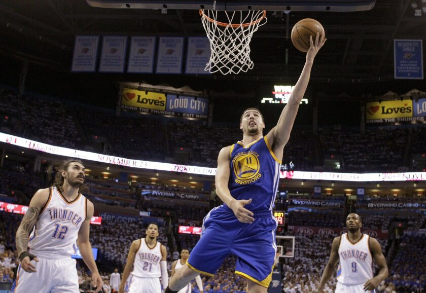 Golden State Warriors guard Klay Thompson (11) shoots against the Oklahoma City Thunder during the first quarter in Game 3 of the NBA basketball Western Conference finals  in Oklahoma City, Sunday, May 22, 2016. (AP Photo/Sue Ogrocki