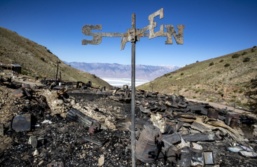 A weather vane blackened by fire stands among charred debris on a dry, brushy mountainside above a desert valley