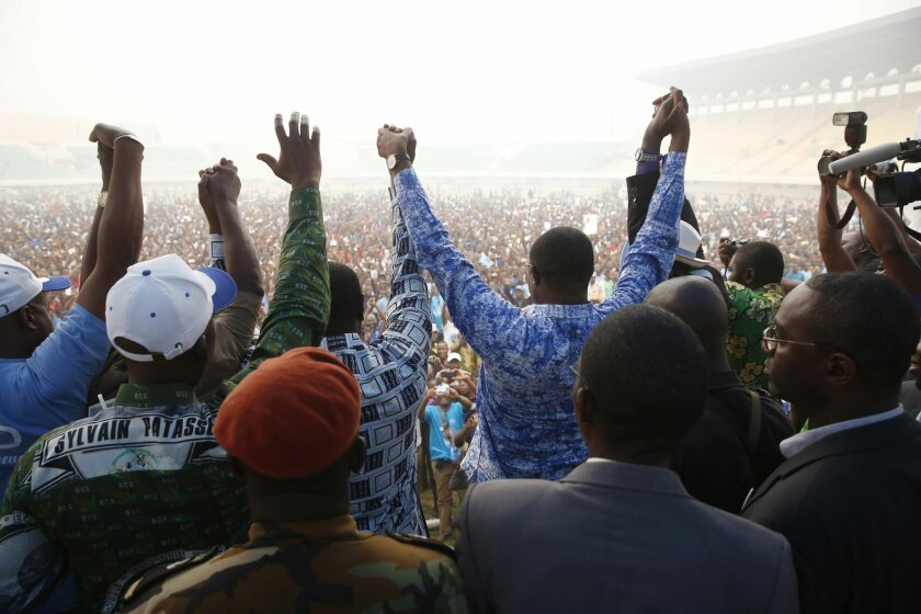 Presidential candidate Anicet Georges Dologuele, wearing a blue shirt centre right, greets the crowds at the national stadium in Bangui, Central African Republic,  Friday Feb. 12, 2016.  Two former prime ministers,  Faustin Archange Touadera and  Dologuele, are running neck-and-neck in the second r