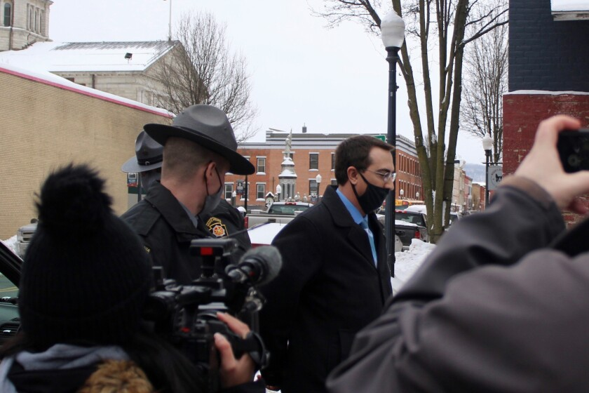 FILE - In this Feb. 3, 2021 file photo, Bradford County, Pa., District Attorney Chad Salsman is escorted into Magisterial District Court, in Towanda, Pa. Salsman pleaded guilty Friday, May 7 to witness intimidation, promoting prostitution and obstruction of justice and resigned from office. (Brianne Ostrander/The Daily Review via AP, File)