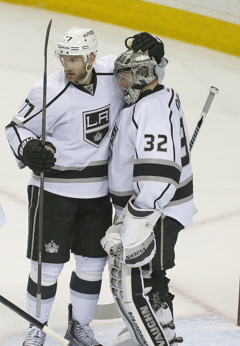 Los Angeles Kings goalie Jonathan Quick (32)  is congratulated by teammate Jeff Carter (77) after a 3-0 victory against the San Jose Sharks in Game 4 of an NHL hockey first-round playoff series in San Jose, Calif., Saturday, April 26, 2014. Los Angeles won 3-0.  (AP Photo/Tony Avelar)