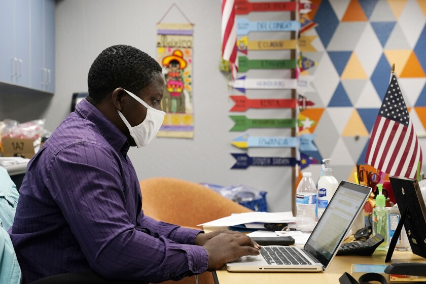 Teaching assistant Samuel Lavi helps out with an online class at the Valencia Newcomer School, Tuesday, Sept. 2, 2020, in Phoenix. Communicating during the coronavirus pandemic has been trying for parents and students at the Phoenix school for refugees who speak a variety of languages and are learning to use technology like iPads and messaging apps.(AP Photo/Ross D. Franklin)