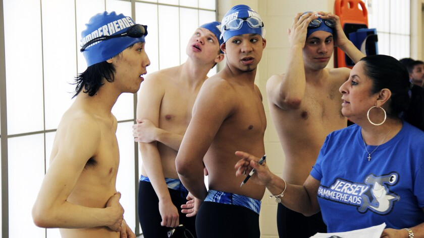 Kelvin Truong (L), Robert Justino (hands behind back), and Mikey McQuay, Jr. (hands on head) listen