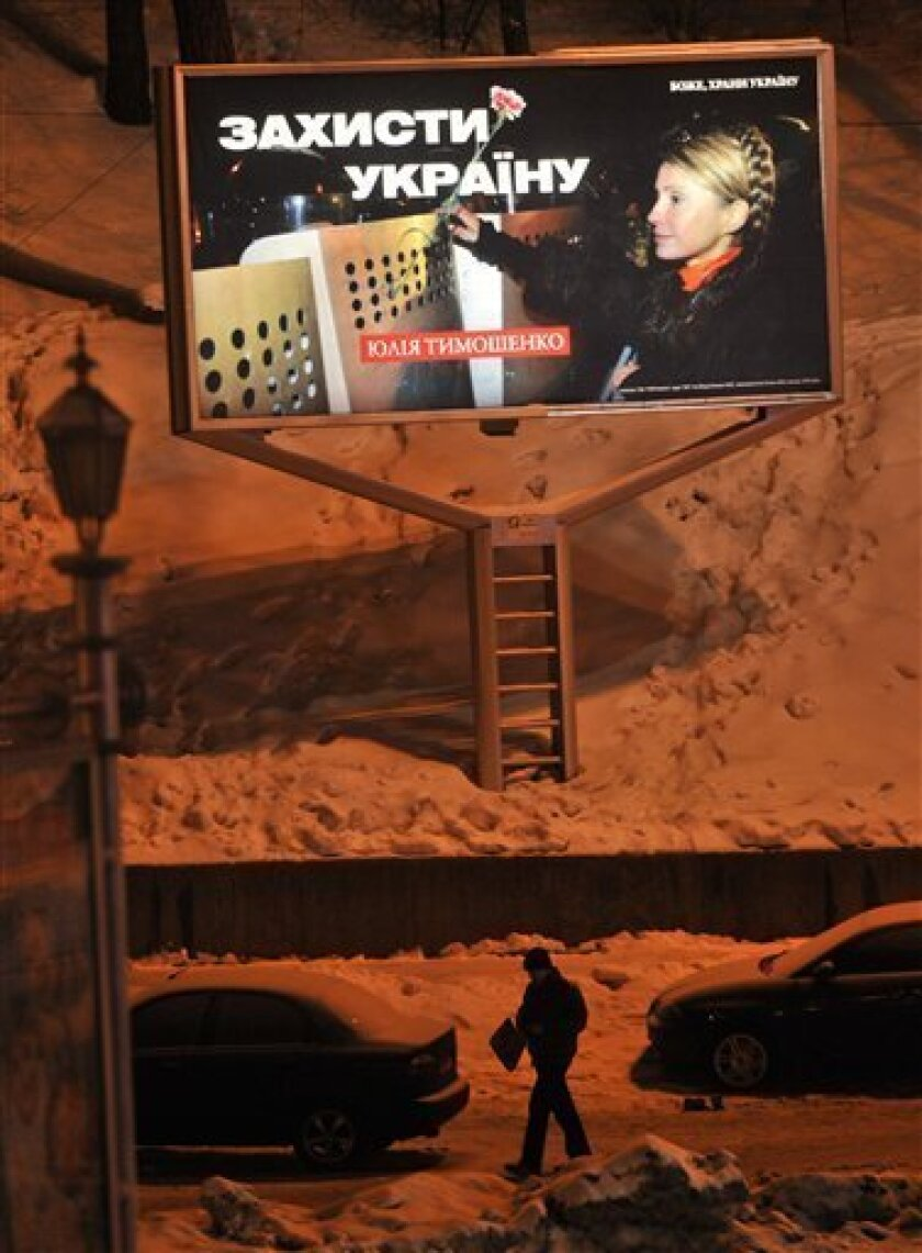 """A man walks past an election poster of Ukraine's Prime Minister Yulia Tymoshenko in the snow in Kiev, Ukraine, Wednesday, Feb. 3, 2010. The poster reads """"Defend Ukraine."""" The second round of voting in Ukraine's presidential election is scheduled for Sunday, Feb. 7. (AP Photo/Sergei Chuzavkov)"""